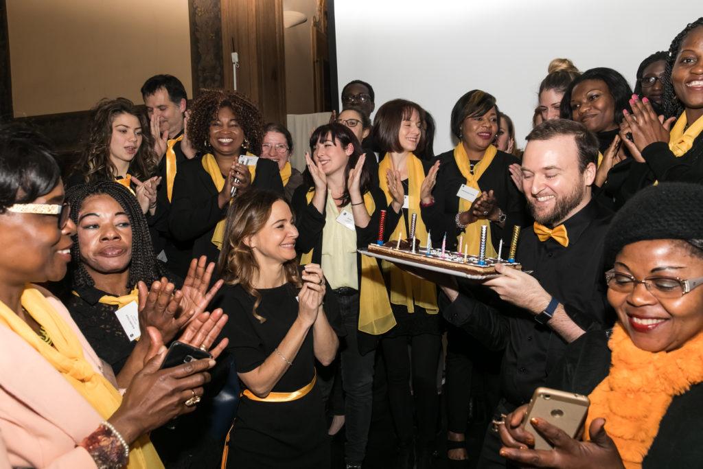 Dafna Mouchenik et son équipe qui applaudissent l'arrivée du gâteau des 10 ans
